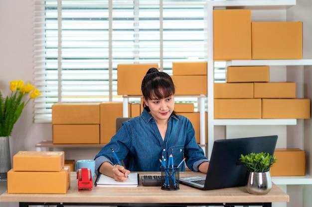 Charmante mooie aziatische tiener eigenaar zakenvrouw werken thuis voor online winkelen, op zoek naar de volgorde in laptop en notitie in haar boek met kantoorapparatuur, ondernemer lifestyle concept Premium Foto