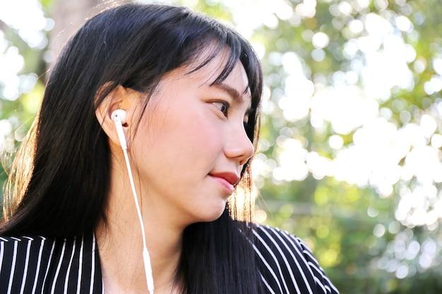 Charmante mooie tan huid aziatische zakelijke vrouw hand gebruik telefoon en luister lied muziek van koptelefoon op kamer. presentatie van uw product Premium Foto