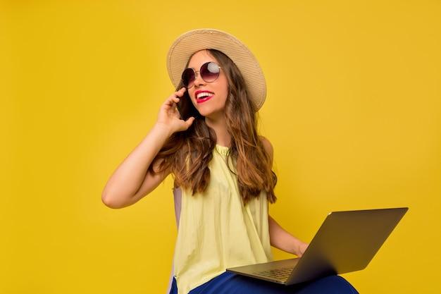 Charmante mooie vrouw zomer hoed en bril praten aan de telefoon en werken met laptop Gratis Foto