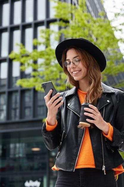 Charmante student boekt hotel online, heeft reis in de grote stad, gericht op smartphone Gratis Foto