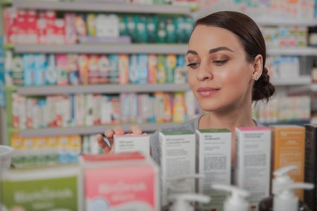 Charmante vrouw die bij apotheek winkelt Premium Foto