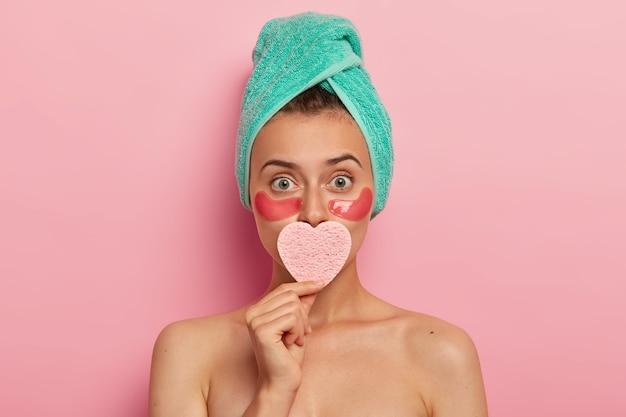 Charmante vrouw heeft minimale make-up, brengt cosmetische sponzen onder de ogen aan, bedekt de mond met een hartvormige spons, heeft een perfect verzorgde huid, ziet er verrassend uit, staat binnen met naakt lichaam Gratis Foto