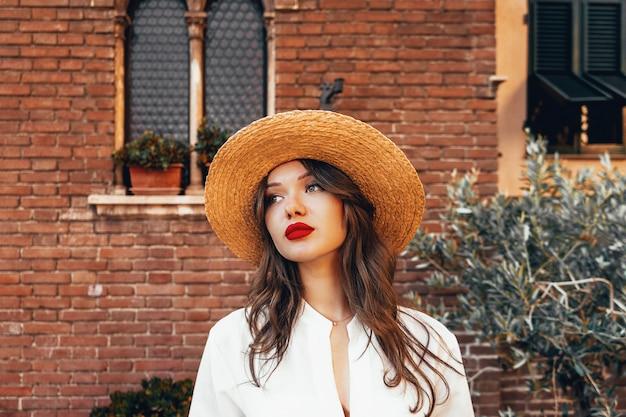 Charmante vrouw in witte blouse en strohoed. portret van make-up meisje met lang haar en grote rode lippen. make-upkit, zomersfeer, concept van pure perfecte huid. schoonheid vakantie concept Premium Foto