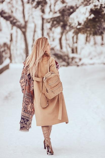 Charmante vrouw loopt in de straat in de winter Gratis Foto
