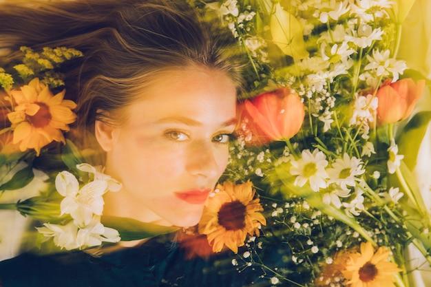 Charmante vrouw tussen verse bloemen in groenheid Gratis Foto