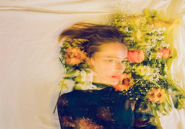 Charmante vrouw tussen verse bloemen op bed Gratis Foto