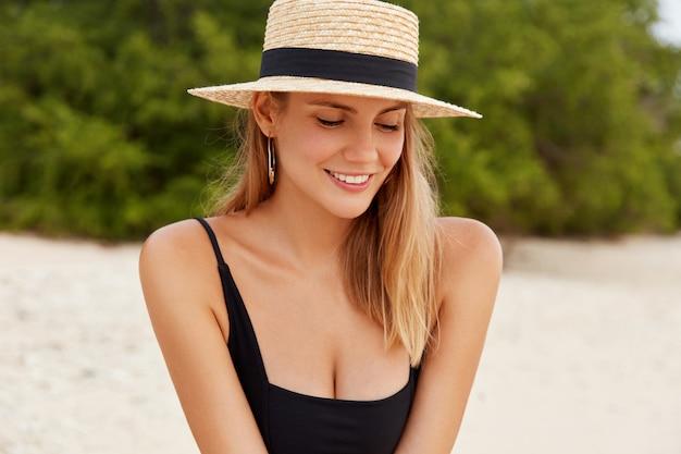 Charmante vrouwelijke toeristen in modieuze hoed kijkt verlegenheid naar beneden, glimlacht vreugdevol, draagt badpak, rust na een actieve wandeling of zwemmen in de oceaan, Gratis Foto