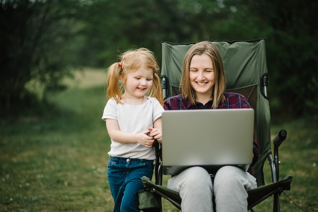 Chat online met familie op laptop op picknick in de natuur. thuisonderwijs, freelance baan. moeder en kind. moeder werkt op internet met kind buitenshuis. Premium Foto