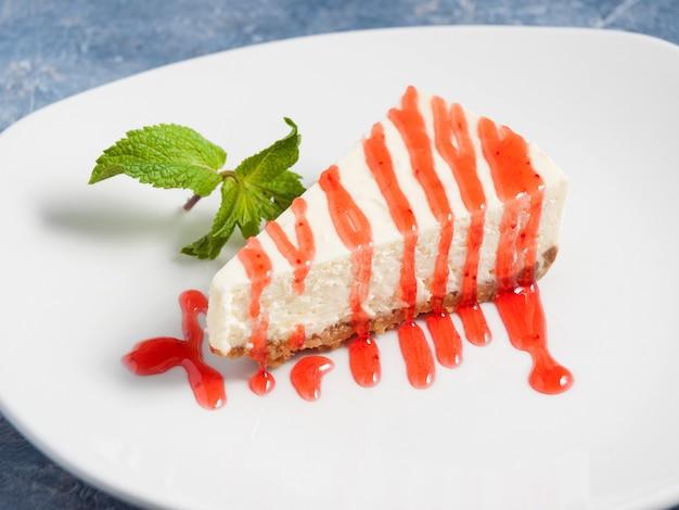 Cheesecake met aardbeiensaus, gegarneerd met munt op een witte plaat Premium Foto