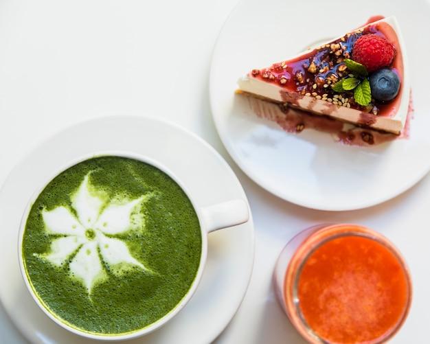 Cheesecake met bessen; smoothie en kopje matcha latte kunst op witte achtergrond Gratis Foto