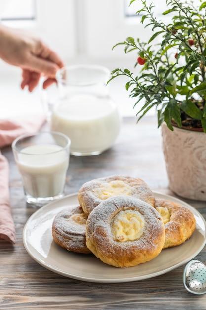 Cheesecake rolt voor het ontbijt op een houten tafel bij het raam met een kat Premium Foto