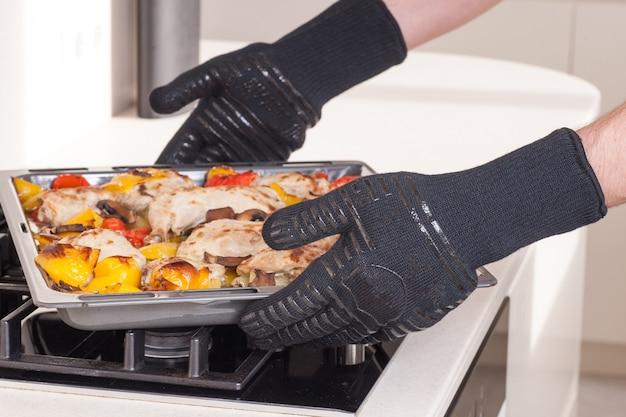 Chef haalt de hete bakplaat in beschermende handschoenen uit de oven Premium Foto