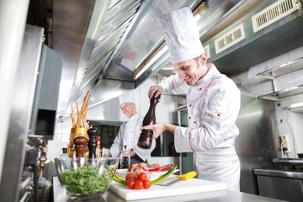 Chef-kok bereidt een gerecht in de keuken van het restaurant Premium Foto