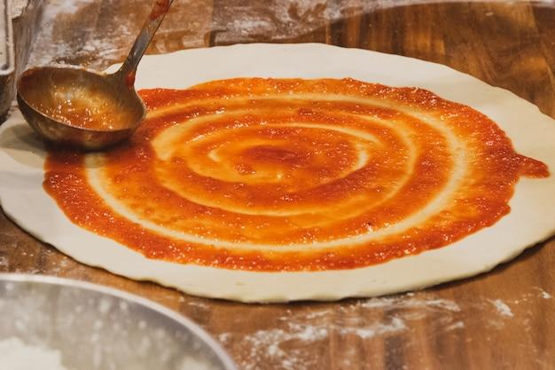 Chef-kok bereidt heerlijke pizza op de keuken Premium Foto