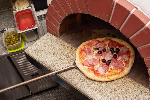 Chef-kok bereidt pizza in traditionele bakstenen oven. Premium Foto