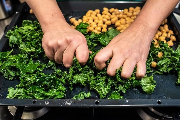 Chef-kok die een gerecht van boerenkool en kekers voorbereidt. Premium Foto