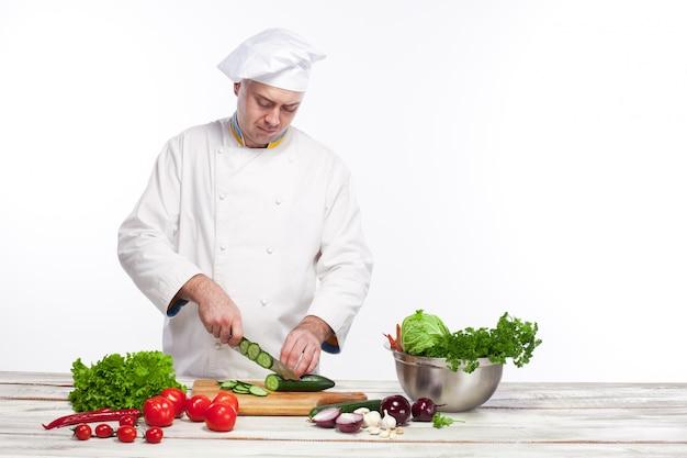 Chef-kok die een groene komkommer in zijn keuken snijdt Gratis Foto