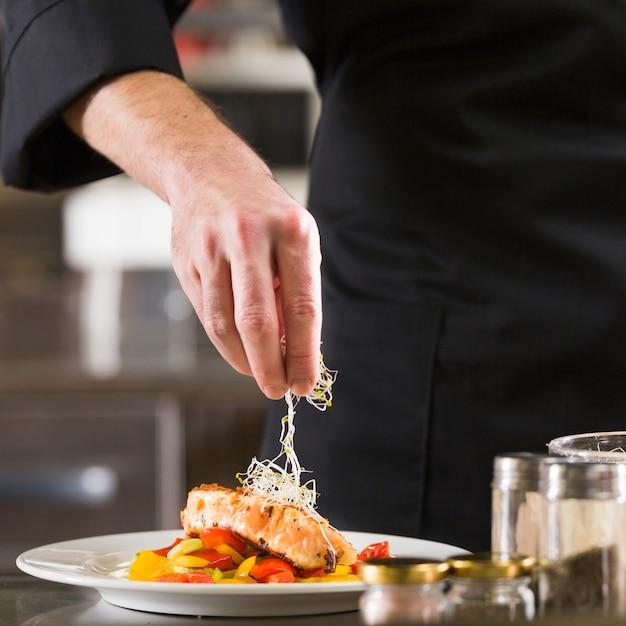 Chef-kok die een schotel van gezond voedsel voorbereidt Gratis Foto