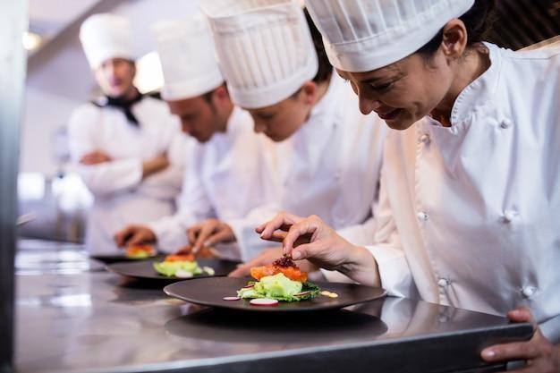 Chef-kok die een voedselplaat verfraait Premium Foto