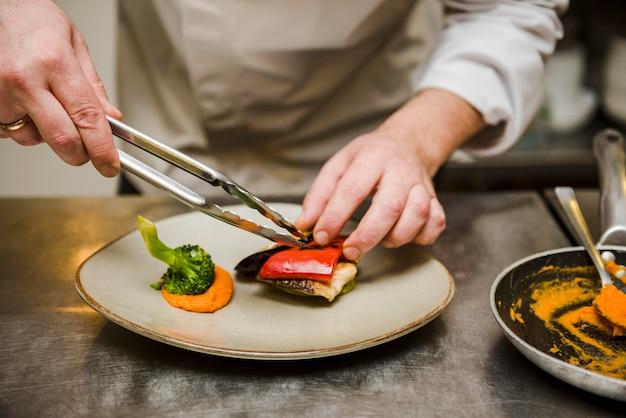 Chef-kok die gastronomisch schotel vooraanzicht voorbereidt Gratis Foto