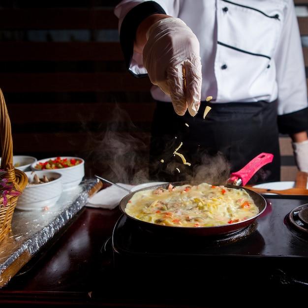 Chef-kok die heerlijke maaltijd in een keuken zijaanzicht voorbereiden Gratis Foto