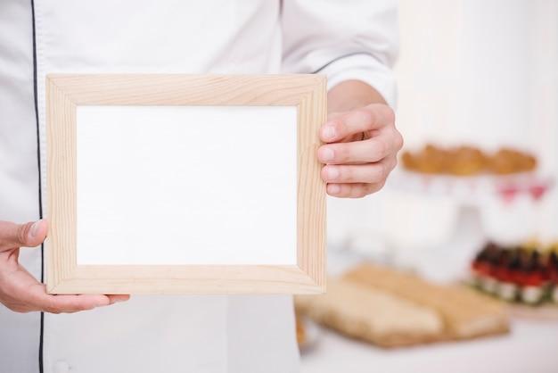 Chef-kok die houten frame met model voorstelt Gratis Foto