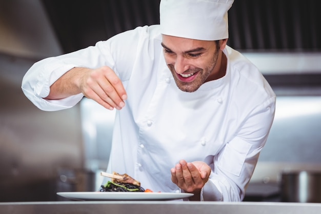 Chef-kok die kruiden op schotel bestrooien Premium Foto