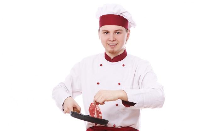 Chef-kok die vers vlees op een pan zet Gratis Foto
