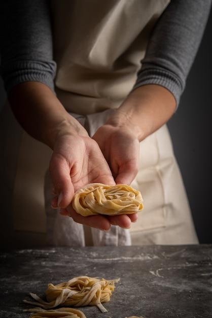 Chef-kok die verse deegwaren houdt Gratis Foto