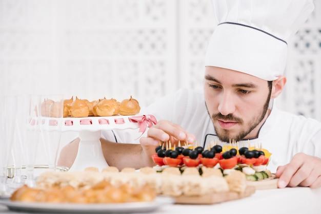Chef-kok die zorgvuldig snacks op een lijst voorbereidt Gratis Foto