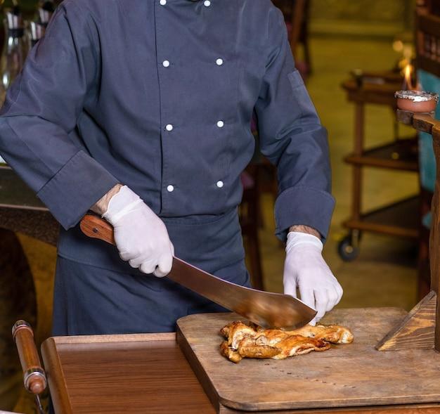 Chef-kok een kippenvlees snijden met een hakmes op de houten plaat Premium Foto