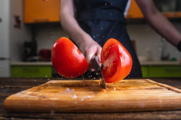 Chef-kok een rode tomaat doormidden snijden met een groot mes in beweging Premium Foto