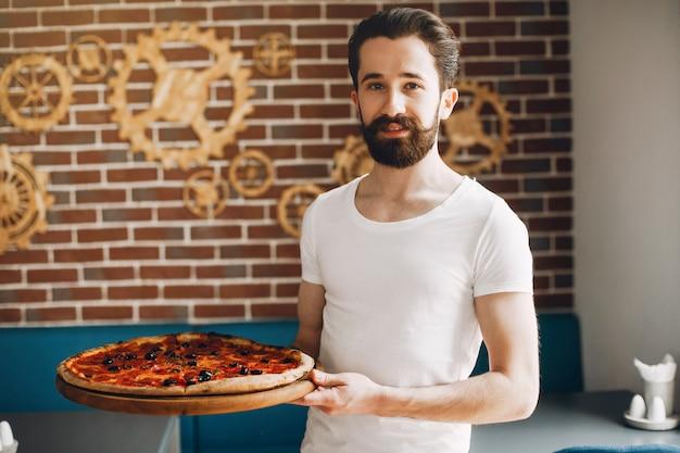Chef-kok in de keuken bereidt pizza Gratis Foto