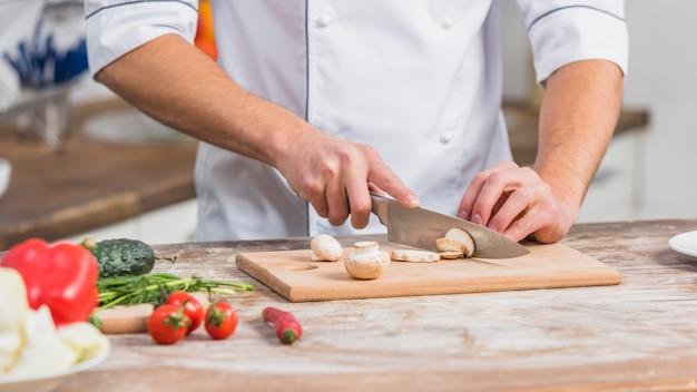 Chef-kok in de keuken koken met groenten Gratis Foto