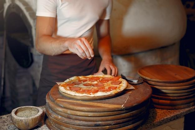 Chef-kok in een witte uniform bereiden een pizzaa Gratis Foto
