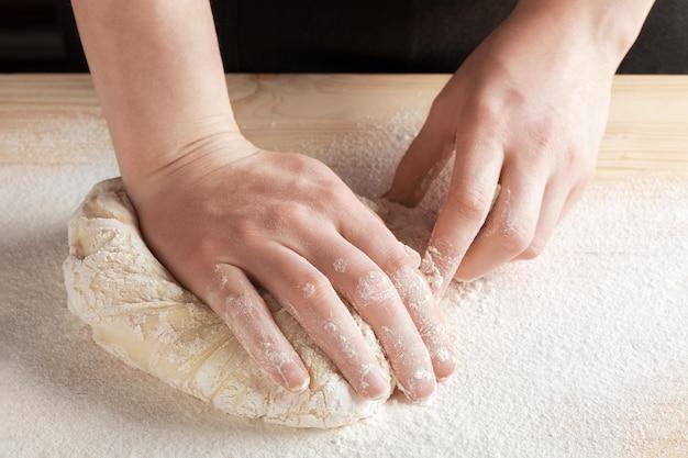 Chef-kok kneedt het deeg voor het bakken Premium Foto