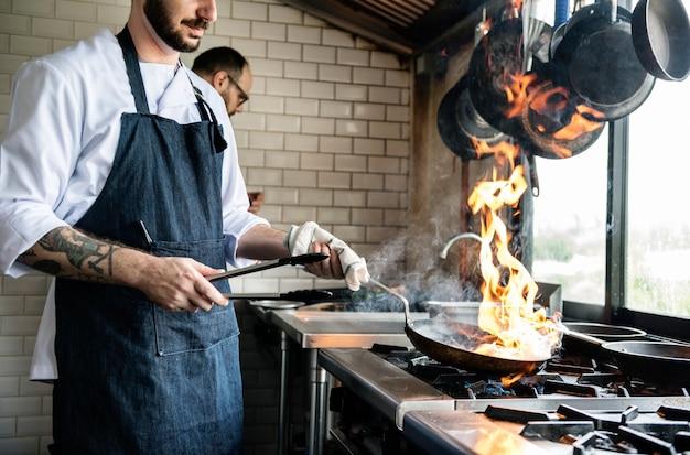 Chef-kok kokend voedsel in de restaurantkeuken Gratis Foto