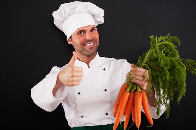 Chef-kok met bos van wortelen duimen opdagen Gratis Foto