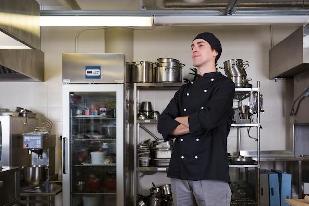 Chef-kok met uniform en keuken Gratis Foto