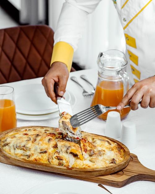 Chef-kok serveert lamsgerecht bedekt met gesmolten kaas Gratis Foto
