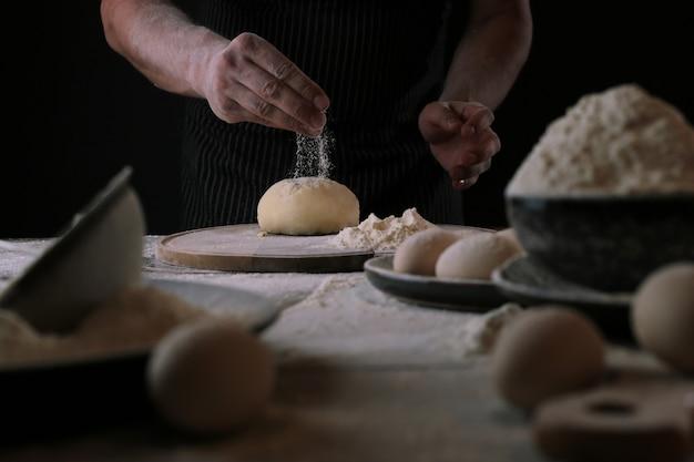 Chef-kok tijdens het maken van een pizzadeeg Gratis Foto