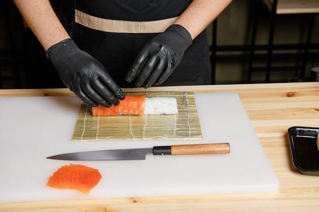 Chef-kok zet zalm tijdens het bereiden van broodjes Premium Foto