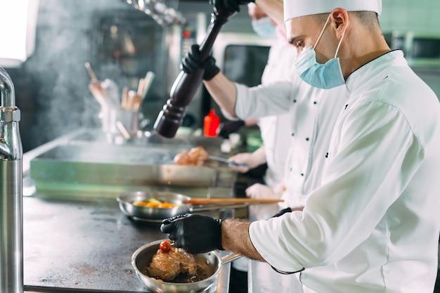 Chef-koks in beschermende maskers en handschoenen bereiden eten in de keuken van een restaurant of hotel. Premium Foto