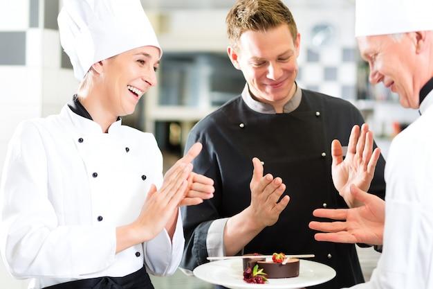 Chef-kokteam in restaurantkeuken met dessert Premium Foto