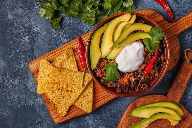 Chili con carne in kom met avocado en zure room Premium Foto