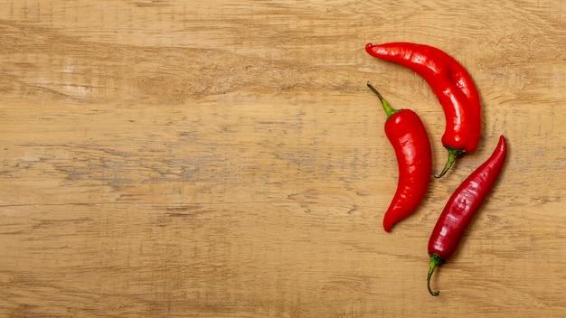 Chili peppers op houten bureau Gratis Foto
