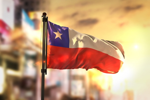 Chili vlag tegen stad wazige achtergrond bij zonsopgang achtergrondverlichting Premium Foto