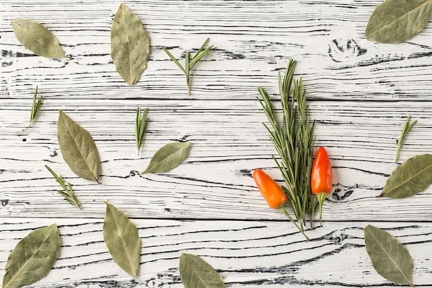 Chilipeper en rozemarijntwijgen met laurierbladeren op houten t Premium Foto