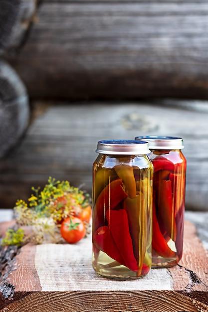 Chilipepers in een glazen pot op een houten tafel, zelfgemaakte augurken Premium Foto