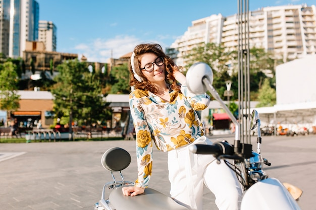 Chillen jonge dame in vintage blouse met bloemmotief zittend op de bromfiets en luistert naar muziek met bomen en wolkenkrabbers Gratis Foto